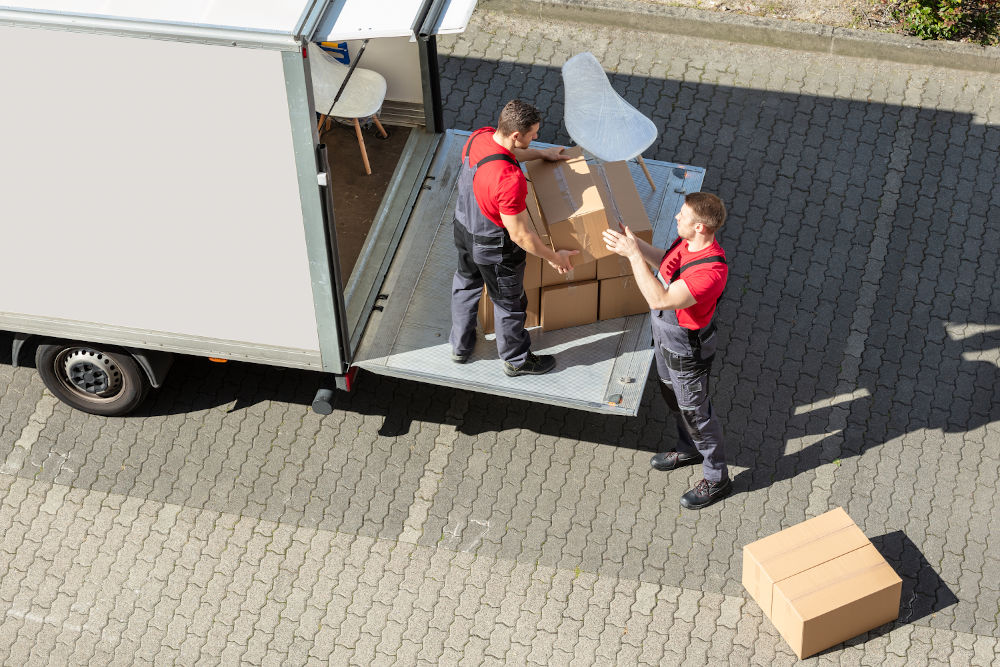 picture of two removal comapny employees loading a furniture into a van