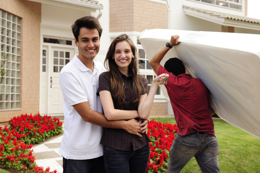 picture of house removals company employee carying matress in front of smiling house owners