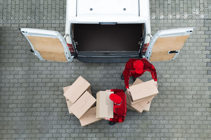 picture of two men carrying boxes unloading van