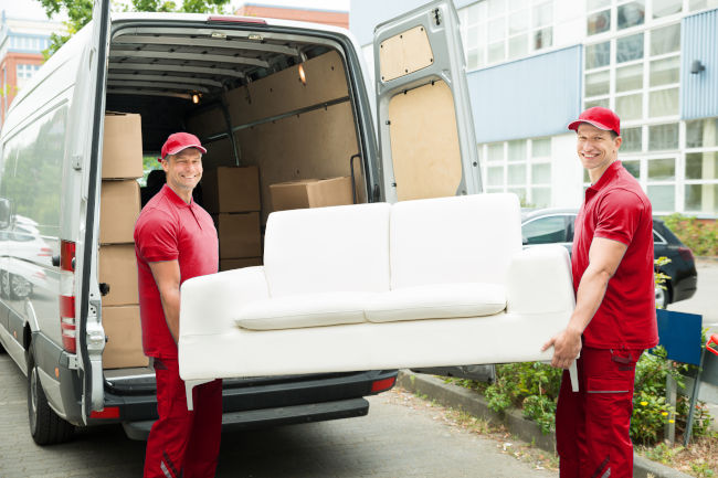 picture of two removal company employees loading sofa into a van