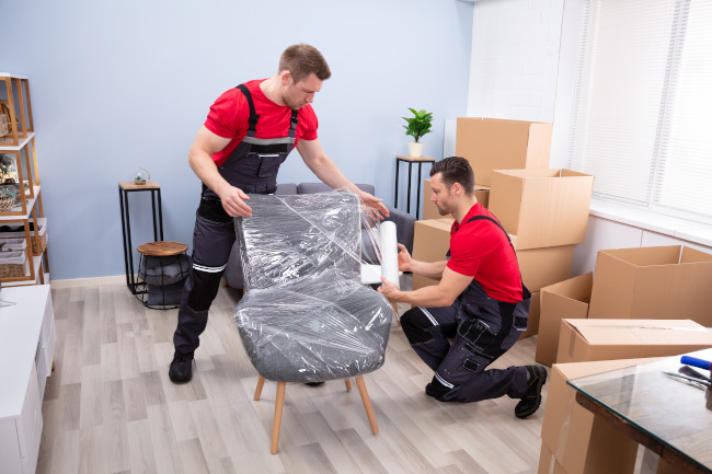 picture of two removal company employees during wraping and packing furniture